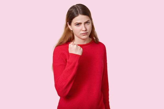 真っ黒な髪の悲しい怒っている若いヨーロッパ女性の写真は赤いジャンパーに身を包んだカメラで拳を示し、バラ色の壁にポーズをとって脅迫し、非難し、復讐することを約束します。