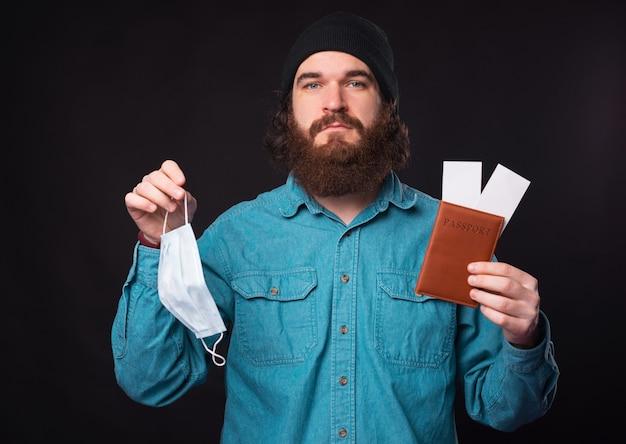 パスポートと飛行機のチケットと薬用フェイスマスクを持っている悲しいひげを生やした男の写真