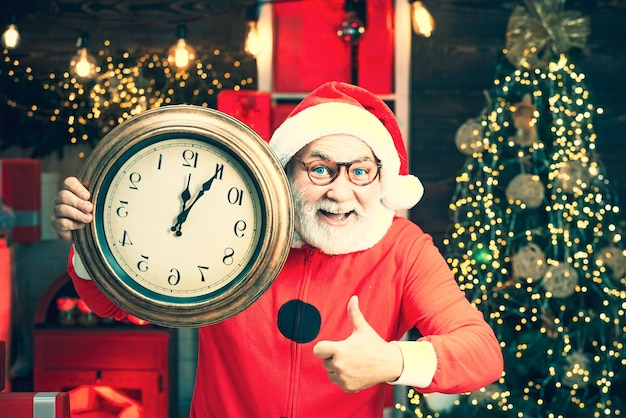 Фотография санта держит часы, показывающие без пяти минут до полуночи. портрет удивленного и смешного санта