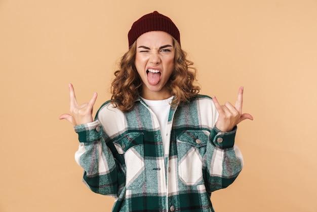 ベージュで隔離された指でウィンクと角を作るニット帽の生意気な若い女性の写真