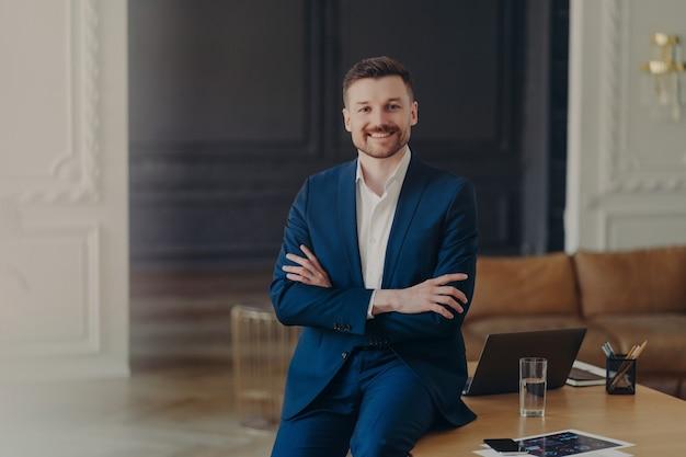 Фотография довольного бородатого преуспевающего бизнесмена уверенно стоит в собственном кабинете или современном офисе со скрещенными руками одет, формально улыбается, приятно доволен результатами своей работы