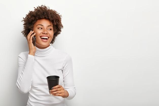 곱슬 머리를 가진 만족스런 평온한 여성의 사진, 스마트 폰을 통해 이야기하고, 긍정적으로 보이고, 테이크 아웃 커피를 마시고, 활기찬 대화 중에 좋은 분위기에 있습니다. 사람과 생활 방식