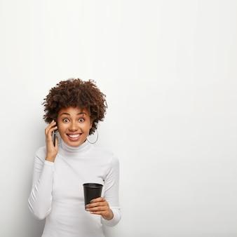 満足している巻き毛のヒップスターの女の子の写真は、携帯電話の会話中に良いニュースを取得します