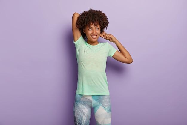 満足している暗い肌の女性の写真は、手を伸ばし、フィットネストレーニングの前にウォームアップし、スポーツウェアを着用し、柔軟性があり、脇に焦点を合わせ、紫色の壁に隔離されています。ワークアウトの概念
