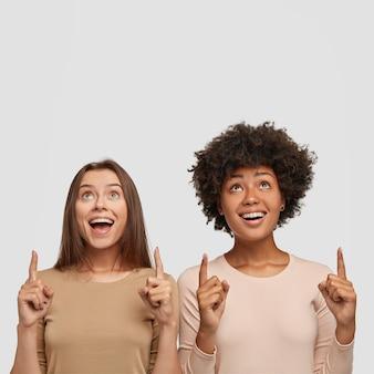 Фотография довольных женщин смешанной расы с радостным выражением лица указывает вверх обоими указательными пальцами, сфокусированными вверх