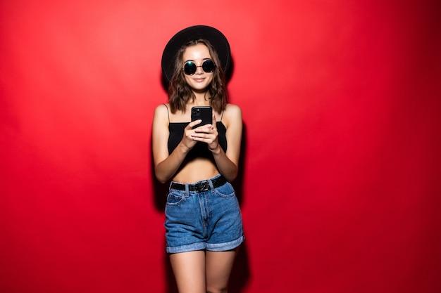 Фотография довольной женщины, использующей мобильный телефон с радостью, изолированной над красной стеной