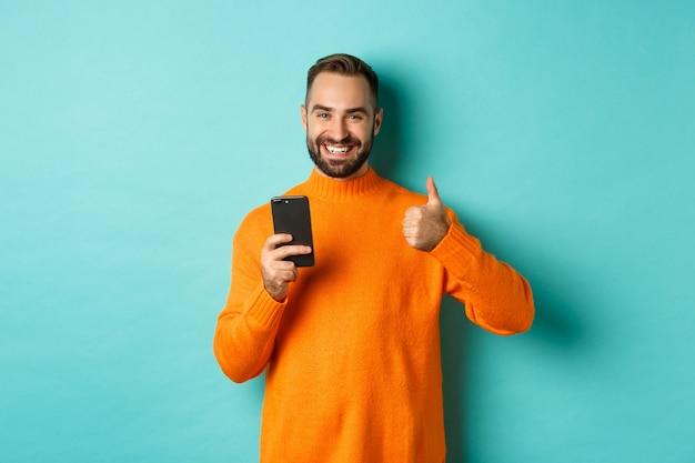 오렌지 스웨터에 만족 된 젊은 남자의 사진, 청록색 배경에 대해 기쁘게 서 휴대 전화에서 읽은 후 엄지 위로 보여주는.