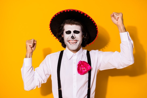 무서운 좀비 남자가 손을 들고 쾌활한 눈을 감은 사진은 프리미엄 장소 문화 축제에서 흰색 셔츠 죽음 의상 설탕 두개골 멜빵 고립 된 노란색 배경을 얻습니다.