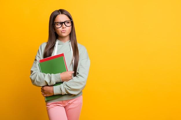 깊은 사려 깊은 빈 공간을 찾고 있는 여학생의 사진은 노란색 배경에 캐주얼하게 격리된 책을 유지합니다