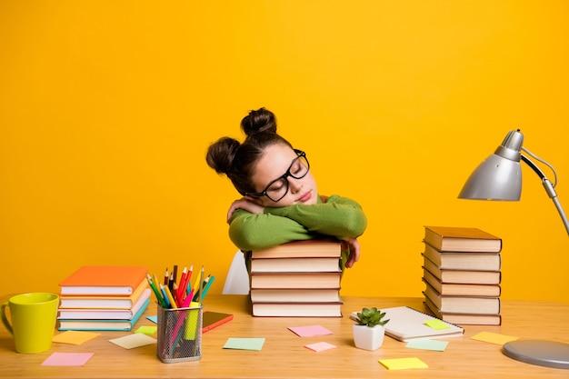 Фотография школьницы сидеть головой стола на книге расслабиться, изолированные на желтом фоне