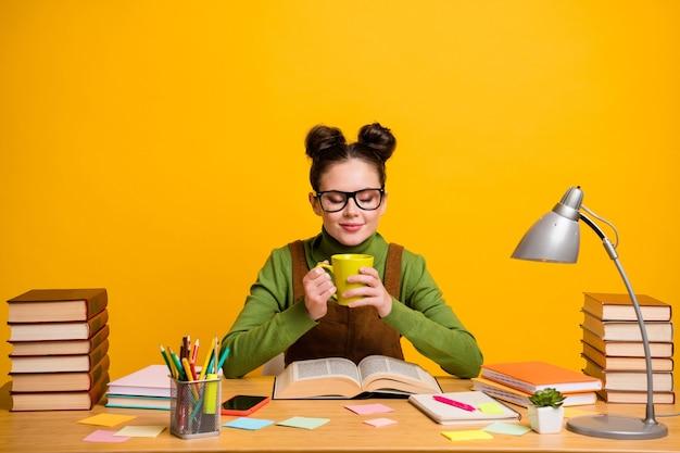 Фотография школьницы сидит за столом, держит чашку кофе, читает учебник на желтом фоне