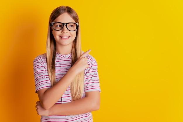黄色の背景で隔離の空白のスペースを指す女子高生の写真