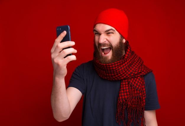 Фотография кричащего бородатого парня в красной шапке и шарфе с помощью мобильного телефона