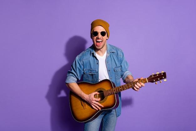 紫紫の鮮やかな色の背景の上に孤立した後ろの壁に影を落とす無精ひげ陽気なハンサムな魅力的なミュージシャンの叫びの写真