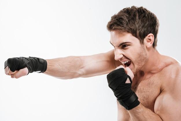Фото кричащего боксера молодого человека делают упражнения бокса над белой стеной. посмотри в сторону.