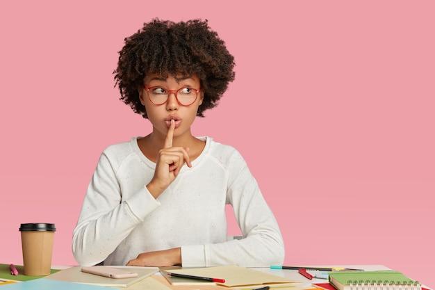 Фотография секретной темнокожей женщины-архитектора жестом молчания в прозрачных очках.