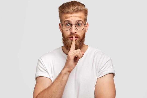 秘密の生姜のスタイリッシュな男性の男の写真は沈黙の兆候を示し、表情を驚かせ、秘密を明かすことを恐れ、カジュアルな服装で、白い壁に一人でポーズをとる。人と秘密の概念