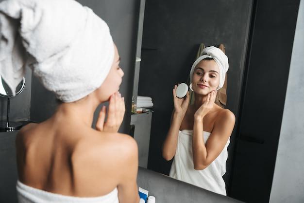 얼굴에 크림을 바르는 수건에 싸여 매혹적인 여자의 사진
