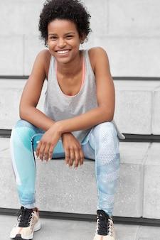 운동복을 입은 자신감있는 흑인 여성의 사진은 행복하고 편안한 표정을 가지고 있으며 광범위하게 미소를 지으며 스포츠 대회에서 승리하고 계단에 앉아 새로운 목표를 달성 할 준비가되었습니다. 민족성, 스포츠