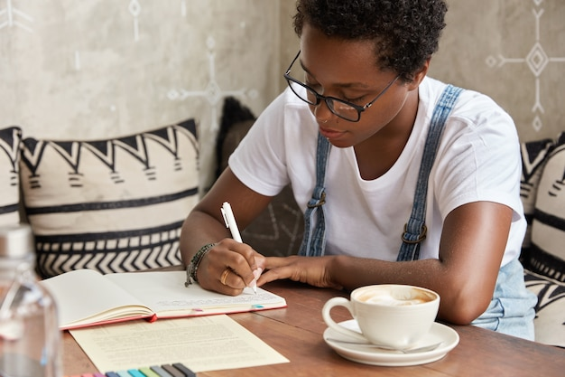 自営業の黒人プロの若い起業家の写真は、ノートブックで彼女のビジネスを発展させるための良いアイデアを書いています