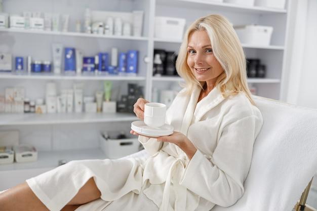 美容院でお茶を持って、白いバスローブで笑っている白人女性のシニアの写真。
