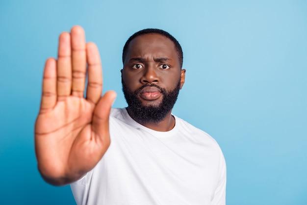 Фотография серьезного африканского человека, шоу ладоней, стоп сигнал, взгляд камеры, в белой футболке на синем фоне