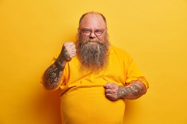 진지한 화난 남자의 사진은 두꺼운 수염을 가지고 주먹을 움켜 쥐고 분노한 표정으로 보이며 복수하겠다고 약속하며 튼튼한 큰 배를 보여주고 노란색 티셔츠를 입고 부정적인 감정을 표현합니다.