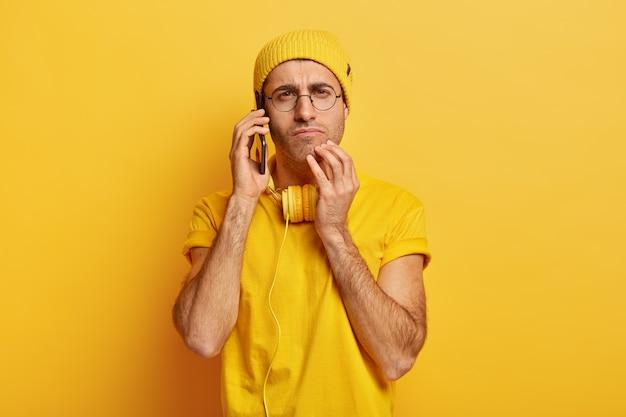 真面目で気配りのある若い男の写真は、電話で会話し、現代の携帯電話を耳の近くに保ち、ヘッドフォンを持っています