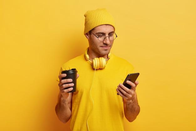 真面目な集中男性の写真は携帯電話を注意深く見て、オンラインでニュースを読み、現代の携帯電話を持っています