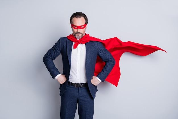 Фото серьезного уверенного смелого настроения профессионального зрелого делового парня с оружием в руках корпоративная вечеринка костюм супергероя носить синий костюм красный плащ с маской для лица изолированный серый фон