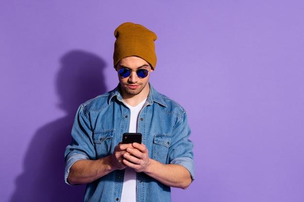 紫色の鮮やかな色の背景で隔離の新しい情報を探してインターネットを閲覧している彼の手で電話を保持している深刻な自信を持ってフリーランサーの写真