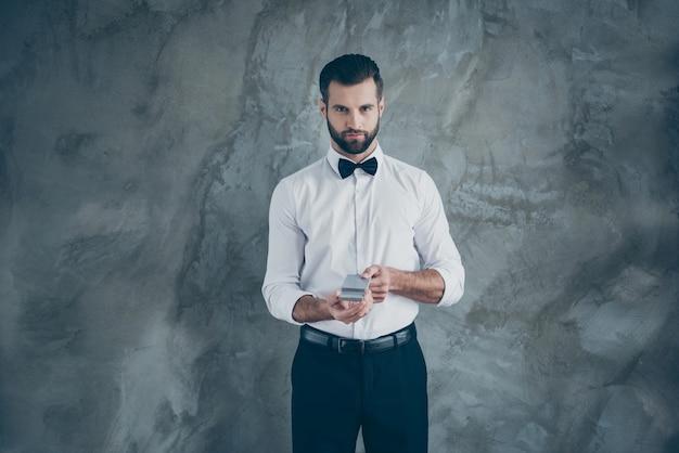 심각한 자신감 남자의 사진은 회색 벽 콘크리트 색 벽 위에 고립 된 포커 게임을 시작하기 위해 준비하는 강모와 함께 더 날카로운 croupier 카드 마스터 수염