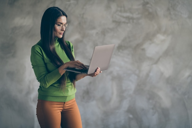 Фотография серьезной, уверенной в себе умной умной женщины, просматривающей ноутбук в оранжевых штанах, печатающей в поисках необходимой информации, изолировала серый цвет стены бетонный фон