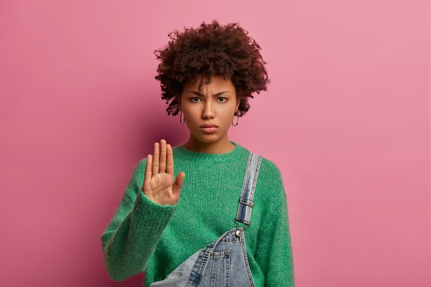 Фотография серьезной кудрявой молодой женщины отвергает странное предложение, вытаскивает ладонь, отклоняет предложение и недовольно смотрит, носит зеленый свитер, предупреждает, чтобы дальше не проходили