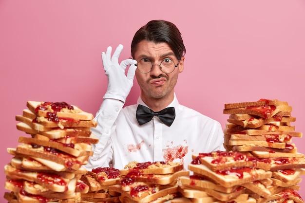 深刻な不満を持った男性レストランの労働者の写真は、眼鏡の縁に手を置き、綿密に見え、ジャムで汚れた白い制服を着て、乾杯の大きなスタックの近くに立っています。サービスコンセプト