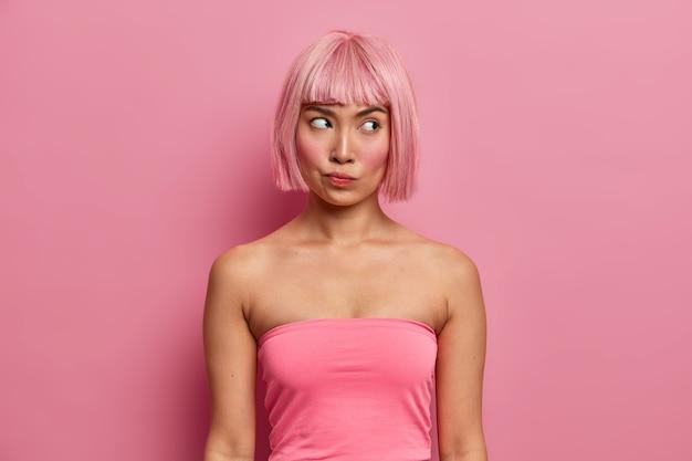 분홍색 탑을 입은 밥 헤어 스타일을 가진 진지한 불쾌한 여성의 사진은 옆으로 쳐다보고 제안에 대해 진지하게 생각하며 성가신 상황을 해결하는 방법을 찾고 결정을 숙고합니다.