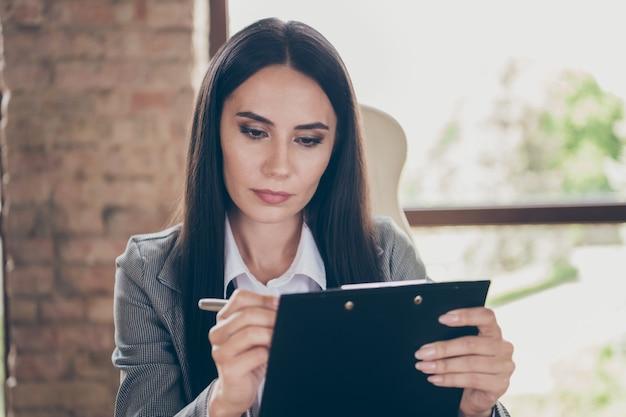 真面目なエグゼクティブ女性の写真は、職場のワークステーションで就職の面接オンラインウェブカメラ会議書き込みクリップボードコーチングウェアブレザージャケットスーツを持っています