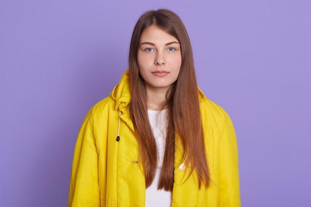 真面目な女性の写真、倦怠感、黄色のジャケットを着て、動揺した表情、長いストレートの茶色の髪の少女、薄紫色の背景の上に隔離されています。