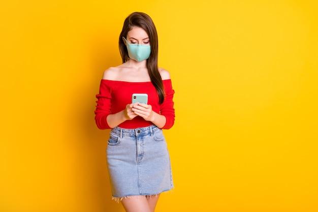 医療マスク使用スマートフォンの深刻な女の子の写真は、ヘルスケアブロガーの投稿を読んでくださいcovid感染ニュースを読んでください明るい輝きの色の背景の上に分離された赤いトップデニムジーンズスカートを着用してください