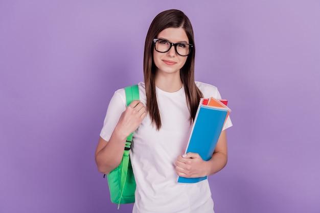 진지한 지적인 대학생 소녀의 사진은 카피북 가방을 들고 보라색 배경에 고립되어 있습니다.