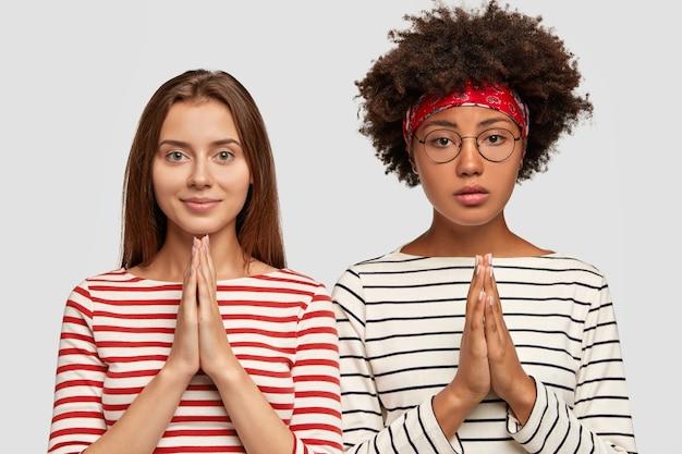 真面目な異人種間の女性の写真は忠実な表現をしていて、手のひらを一緒に押し続けます