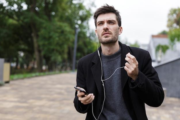 야외를 걷는 동안 휴대 전화를 사용하여 이어폰을 착용 한 심각한 남자 20 대의 사진
