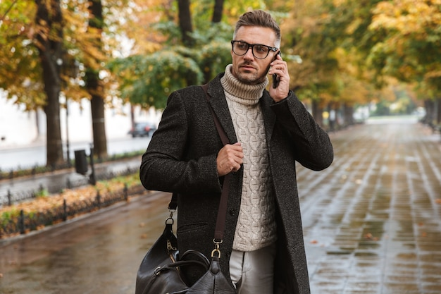 가을 공원을 산책하는 따뜻한 옷을 입고 휴대 전화로 말하는 진지한 30 대 남성의 사진