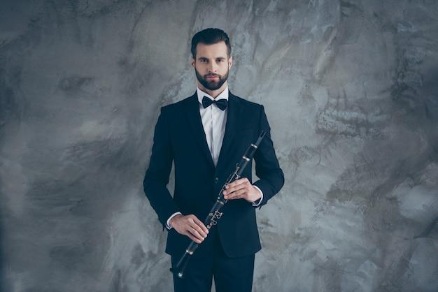 Фотография серьезного профессионального музыканта, готовящегося играть на кларнете с бородой на лице, изолирована серой бетонной стеной