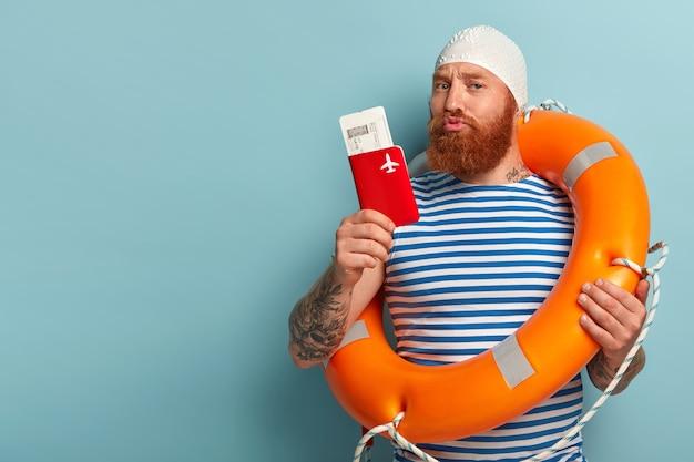 진지한 빨간 머리 남자의 사진은 얼굴을 찡그리고 카메라를 자신있게 바라보고 여행 시간을 말하며 티켓과 함께 여권을 들고