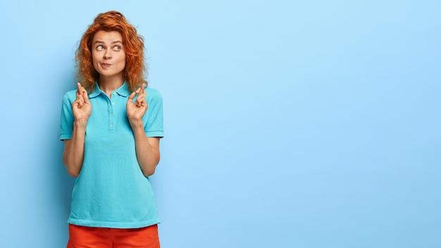 На фото: серьезная рыжеволосая женщина нажимает на губы, держит пальцы скрещенными, молится об успехе, носит синюю футболку, делает знак молитвы