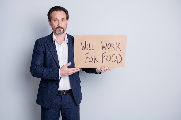 Фотография серьезного грустного бедного бездомного безработного уволенного парня, страдающего финансовым кризисом, потерянной работы, удержания плаката, поисковой работы для некоторых продуктовых обменов, носить синий костюм, изолированный серый фон