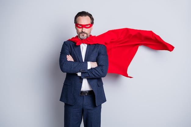 Фото серьезного уверенного в себе крутого профессионала в возрасте зрелого делового парня, скрестив руки на скрещенных руках, тема корпоративной вечеринки, костюм супергероя, синий костюм, красный костюм, маска для лица, плащ, изолированный серый фон
