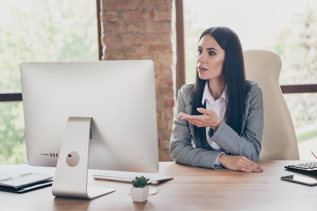 真面目でスマートな成功したエグゼクティブチーフガールの写真座るテーブルワークリモート使用コンピューターpcディスカッションレポートオンライン接続パートナーシップブリーフィングウェアジャケットブレザースーツワークステーション