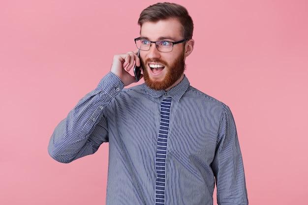彼の電話で電話をかけている眼鏡をかけた真面目な笑顔の幸せな成功したひげを生やした男の写真、広く笑顔、幸せな驚き、ピンクの背景に分離。